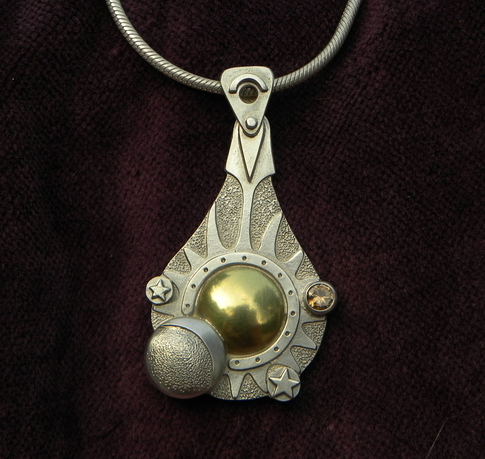 Silver pendant with sun, moon and stars