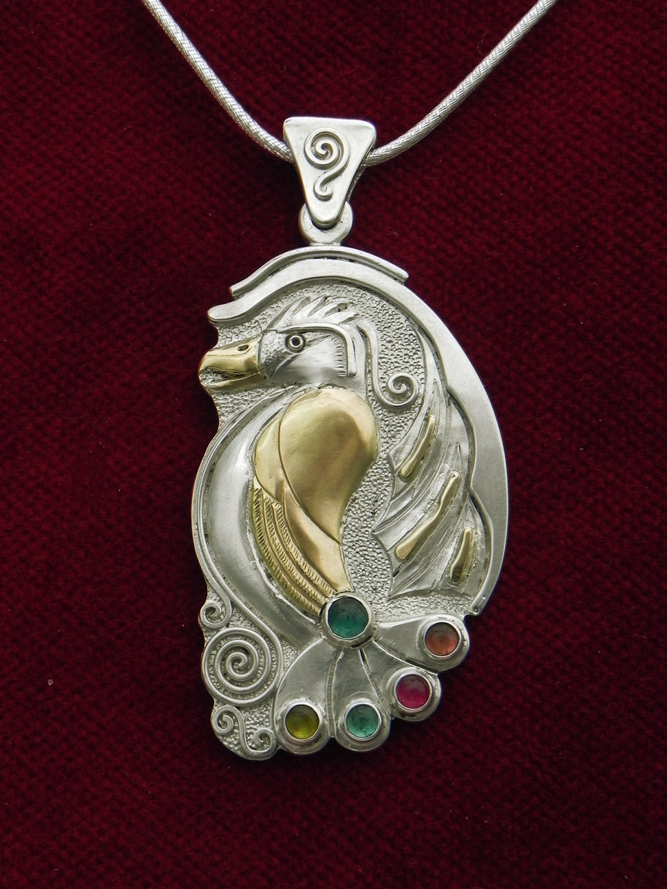 Silverpendant with paradise bird and turmalins